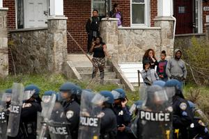 BALTIMORE, MD - APRIL 27:  People in a home look on as Baltimore Police officers stand in the middle of Reisterstown Road near Mowdamin Mall, April 27, 2015 in Baltimore, Maryland. The funeral service for Freddie Gray, who died last week while in Baltimore Police custody, was held on Monday morning. (Drew Angerer/Getty Images)