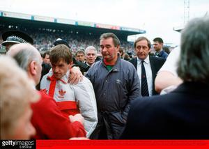 Liverpool Manager Kenny Dalglish is comforted by a police officer, as he and Nottingham Forest Manager Brian Clough leave the pitch. Credit: Bob Thomas/Getty Images