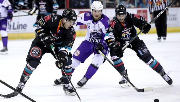 Belfast Giants forwards David Goodwin (left) and Ben Lake (right) battle for possession with Glasgow Clan forward Marcus Jonsson during Saturday night's game at the SSE Arena (William Cherry/Presseye)