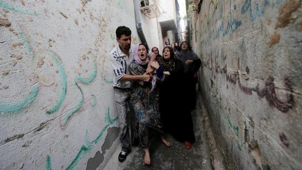 Palestinian relatives cry when mourners carry out the body of Gamal Ielian, 10, who was killed along with 9 other people, all but one of them children, in an explosion at a park at the Shati refugee camp, in the northern Gaza Strip, Monday, July 28, 2014. (AP Photo/Adel Hana)