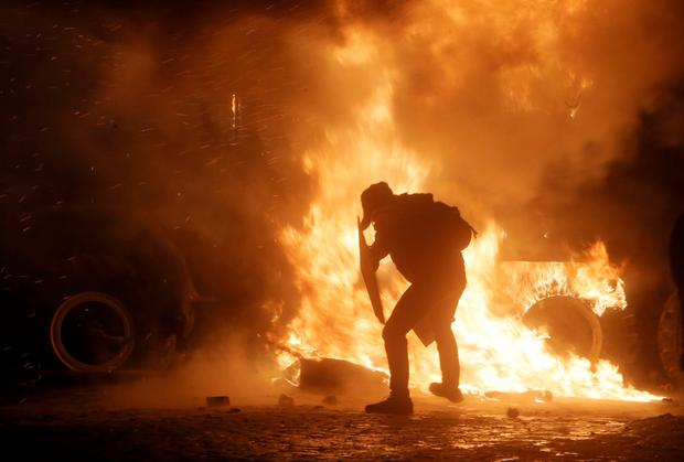 A protester throws a molotov cocktail towards a burning police car, in front of him, during clashes with police, in central Kiev, Ukraine,  early Monday, Jan. 20, 2014. Anti-government protests in Ukraine's capital escalated into fiery street battles with police Sunday as thousands of demonstrators hurled rocks and firebombs to set police vehicles ablaze. Dozens of officers and protesters were injured. (AP Photo /Efrem Lukatsky)