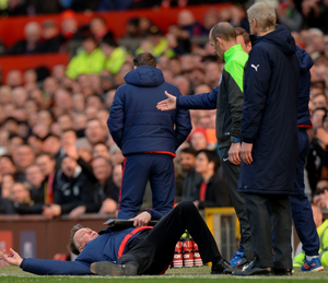 Floored: Louis van Gaal dramatically throws himself to the ground as a protest at alleged diving from Arsenal's Alexis Sanchez