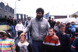 PACEMAKER BELFAST                    AUGUST 1988         PF  GERRY ADAMS WITH ARTIST IN WEST BELFAST JUDGING WALL MURALS, ADAMS PICTURED WITH STICKER SAYING I LOVE WEST BELFAST. ALSO SURROUNDED WITH KIDS.  674/88/BW