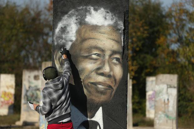 KLEINMACHNOW, GERMANY - OCTOBER 19:  Street artist Victor Landeta spray paints a portrait of former South African leader and human rights activist Nelson Mandela on a sliver of the former Berlin Wall near Berlin on October 19, 2013 in Kleinmachnow, Germany. Ailing Mandela recently spent three months in a hospital and is now receiving treatment at home.  (Photo by Sean Gallup/Getty Images)