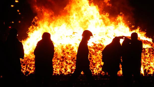 A firefighter attends to  an 11th night Bonfire in the Sandy Row area of Belfast. Pic: Niall Carson/PA Wire