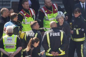 LONDON, ENGLAND - JUNE 15:  Prime Minister Theresa May speaks to members of the fire service as she visits Grenfell Tower, on June 15, 2017 in London, England. At least twelve people have been confirmed dead and dozens missing, after the 24 storey residential Grenfell Tower block in Latimer Road was engulfed in flames in the early hours of June 14. The number of fatalities are expected to rise.  (Photo by Dan Kitwood/Getty Images)