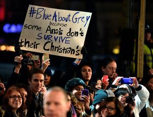 A lone protester holds up a placard as talent arrives for the UK Premiere of 'Fifty Shades of Grey' in central London on February 12, 2015. AFP PHOTO / LEON NEALLEON NEAL/AFP/Getty Images