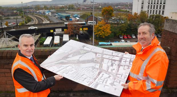 Chris Conway, Translink Group Chief Executive, and Leo Martin, Graham civil engineering managing director at the site of the Belfast Transport Hub with a copy of the masterplan.