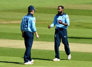 Adil Rashid, right, celebrates with captain Eoin Morgan after taking the wicket of Ireland's Kevin O'Brien (Mike Hewitt/PA)
