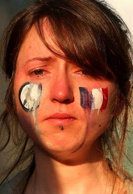 MELBOURNE, AUSTRALIA - NOVEMBER 16:  Tears run down the face of a lady as people gather for a vigil to honour victims of the Paris terror attacks at Federation Square on November 16, 2015 in Melbourne, Australia. 129 people were killed in Paris following a series of terrorist acts in the French capital on Friday night.  (Photo by Quinn Rooney/Getty Images)