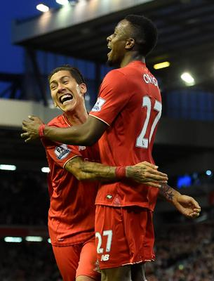 Liverpool's Belgian striker Divock Origi (R) celebrates Liverpool's Brazilian midfielder Roberto Firmino after scoring during the English Premier League football match between Liverpool and Everton at Anfield in Liverpool, north west England on April 20, 2016. AFP/Getty Images