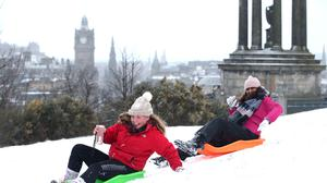 Clara McEwan (left) and Sasha Bey, both aged 17 and from Edinburgh, sledge down Calton Hill overlooking the city (Jane Barlow/PA)