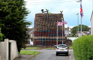 Twelfth bonfire builders at work in Antrim's Ballycraigy estate. Photo: Pacemaker