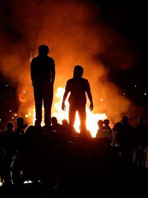 People watch a bonfire, from the top of a cannon on Derry city walls in the bogside area of Londonderry, which is traditionally torched on August 15 to mark a Catholic feast day celebrating the assumption of the Virgin Mary into heaven, but in modern times the fire has become a source of contention and associated with anti-social behaviour. PRESS ASSOCIATION Photo. Picture date: Tuesday August 15, 2017. Disorder flared in Londonderry on Monday night as bonfire-builders attacked police and members of the public. Police said those gathered at the controversial fire site in Derry's Bogside threw rocks and stones at local people before targeting police with petrol bombs and other missiles. See PA story ULSTER Bonfire. Photo credit should read: Niall Carson/PA Wire
