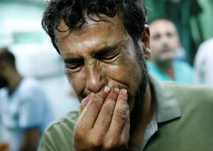 A Palestinian man cries after bringing a child, wounded in an Israeli strike on a compound housing a U.N. school in Beit Hanoun, in the northern Gaza Strip, to the emergency room of the Kamal Adwan hospital in Beit Lahiya, Thursday, July 24, 2014. (AP Photo/Lefteris Pitarakis)
