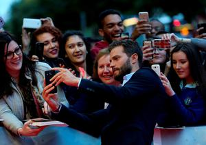 Jamie Dornan poses for photos with fans as he attends the screening of The Siege of Jadotville at the Savoy Cinema in Dublin. PA