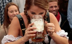 MUNICH, GERMANY - SEPTEMBER 21:  Revellers reach for the first beer mug at Hofbraeuhaus beer tent during day 1 of the Oktoberfest 2013 beer festival at Theresienwiese on September 21, 2013 in Munich, Germany. The Munich Oktoberfest, which this year will run from September 21 through October 6, is the world's largest beer fest and draws millions of visitors.  (Photo by Johannes Simon/Getty Images)