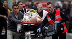 Charlie Hebdo bloodbath: An injured person is evacuated outside the French satirical newspaper Charlie Hebdo's office in Paris following a shooting at the French satirical newspaper. (AP Photo/Thibault Camus)