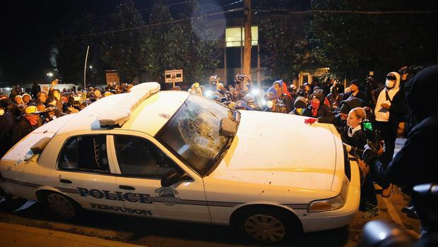 A police squad car is turned over by demonstrators during a protest on November 25, 2014 in Ferguson, Missouri.  (Photo by Scott Olson/Getty Images)
