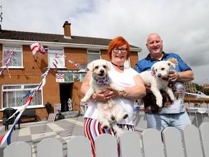 PACEMAKER PRESS BELFAST  13/7/2020 Twelfth of July celebrations in Portadown today as 6 local bands paraded through streets and estates in a socially distanced manner. People were encouraged to celebrate the Twelfth from home as bands brought the celebrations to the people.  Pictured: Kim and Neil Millar with their dogs as they watch the parade. Photo Pacemaker Press