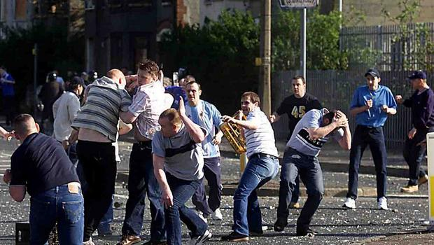 Shankill Road loyalist Winkie Irvine throwing a crate during a 2005 riot at the Ardoyne shops