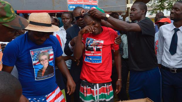 "A ""representative"" in a mock election of US Republican presidential candidate Donald Trump (C) pretends to weep November 08, 2016 following the outcome of a street popularity ballot in Kenya's lakeside town of Kisumu, in which Democratic Candidate Hillary Clinton emerged the winner.  Sentiment at the lakeside town and the country at large appeared to remain strong in favour of US' Democratic party, whose outgoing President, Barack Obama is considered a son given his father's Kenyan heritage, more so at Kogelo, about 60 kilomtres from Kisumu, the birthplace of his father, Obama Snr. / AFP PHOTO / TONY KARUMBATONY KARUMBA/AFP/Getty Images"