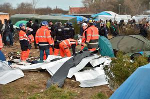 "Workers dismantle shelters on February 29, 2016 in the ""jungle"" migrants and refugees camp in Calais, northern France. Pic Getty Images"