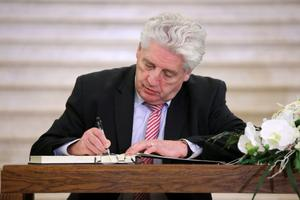 Press Eye - Belfast - Northern Ireland - 15th September 2014 - Picture by Kelvin Boyes / Press Eye.  SDLP leader Dr. Alasdair McDonnell signs a book of condolence at in the Great Hall at Parliament Buildings, Stormont, Belfast, in memory of former DUP leader and First Minister Rev Ian Paisley.   The funeral of Ian Paisley, the former Democratic Unionist Party leader and first minister of Northern Ireland, will take place this week.