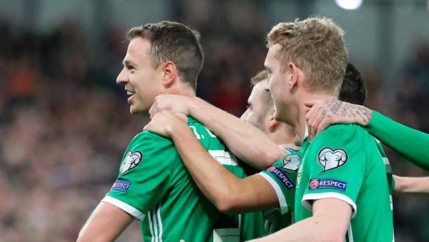 Standing tall: Jonny Evans is mobbed after scoring the opener against Belarus