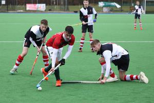 Friends School's Connor Quinn, centre, powers past Wallace High School's Cameron Forrest during the Burney Cup Hockey Semi-Final.  Photo by Peter Morrison