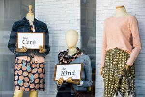 Signs held by mannequins in a closed Belfast clothes stores advising people to Take Care and Be Kind on Tuesday March 24, 2020. Liam McBurney/PA Wire