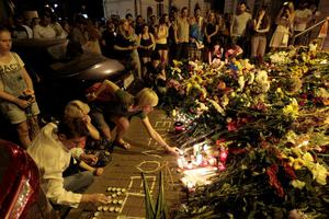 People hold candles and place flower tribute outside the Dutch embassy to commemorate victims of Malaysia Airlines plane crash in Kiev, Ukraine, Thursday, July 17, 2014.  A Malaysian Airlines passenger jet was shot down in eastern Ukraine on Thursday, and both the Ukrainian government and pro-Russian rebels blamed one another for the attack.(AP Photo/Sergei Chuzavkov)