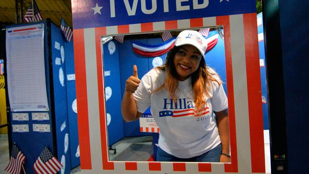A woman, supporter of the Democrat candidate, thumbs up after voting during a straw vote organized for the US Presidential elections on November 8, 2016 during the US election night event in Abidjan. America's future hung in the balance on November 8, 2016 as millions of eager voters cast ballots to elect Democrat Hillary Clinton as their first woman president, or hand power to the billionaire populist Donald Trump. / AFP PHOTO / SIA KAMBOUSIA KAMBOU/AFP/Getty Images