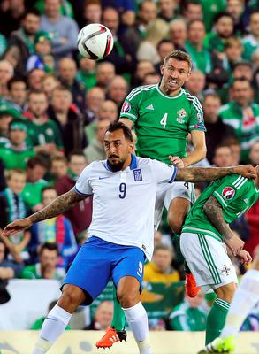 Northern Ireland's defender Gareth McAuley (R) vies for the ball with Greece's forward Kostas Mitroglou  during the UEFA Euro 2016 qualifying Group F football match between Northern Ireland and Greece at Windsor Park in Belfast, Northern Ireland, on October 8, 2015.    AFP PHOTO / PAUL FAITHPAUL FAITH/AFP/Getty Images