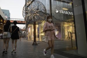 Shoppers pass through an affluent shopping district in Beijing as anti-virus lockdowns were lifted and factories and stores reopened (Ng Han Guan/AP)