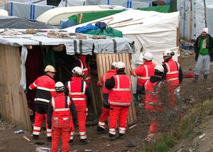 Helmeted workers pull down makeshift structures where migrants sleep in the southern sector of the camp near the northern port of Calais, France, Monday, Feb. 29, 2016. French authorities have begun dismantling the sprawling migrant camp in Calais where thousands are hanging out, hoping to make their way to a better life in Britain. (AP Photo/Chris den Hond)