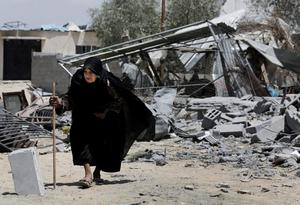 A Palestinian elderly woman walks on the rubble of her destroyed house hit by an Israeli strike in Beit Lahiya, in the northern Gaza Strip, Monday, Aug. 4, 2014. (AP Photo/Adel Hana)