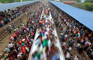 Bangladeshi Muslims travel on the roof of a train to head home ahead of Eid al-Fitr as others wait at a railway station in Dhaka, Bangladesh, Thursday, Aug. 8, 2013. Hundreds of thousands of people working in Dhaka to make a living return home to spend time with their family during Eid al-Fitr. (AP Photo/A.M. Ahad)