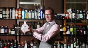 Galgorms resident Gin Connoisseur Marcus Carty in the Gin Library with Galgorm's very own bottle of Watenshi.
