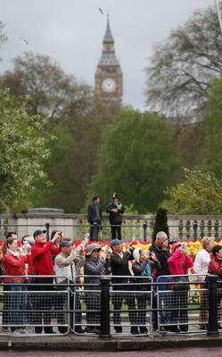 LONDON, ENGLAND - MAY 08:  Crowds near Buckingham Palace photograph a marching band as they wait for HM Queen Elizabeth II to pass in a coach to the State Opening of Parliament  on May 8, 2013 in London, England. Queen Elizabeth II will unveil the coalition government's legislative programme in a speech delivered to Members of Parliament and Peers in The House of Lords today. Proposed legislation is expected to be introduced on toughening immigration regulations, capping social care costs in England and setting a single state pension rate of 144 GBP per week.  (Photo by Peter Macdiarmid/Getty Images)