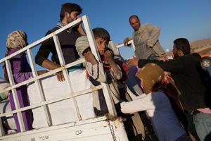 SANLIURFA, TURKEY - OCTOBER 01:  Refugees climb onto a truck to sit to be transported away after crossing the border from Syria into Turkey on October 1 , 2014 near Suruc, Turkey. Kurdish troops are engaged in a battle against fighters of the Islamic State (IS, also called ISIS and ISIL) to defend the strategic nearby Kurdish border town of Kobani (also called Ayn Al-Arab), which ISIS has surrounded on three sides. The Turkish Parliament is due to vote on a measure on October 2, which would allow Turkish ground forces to enter Syria, creating a buffer zone to protect fleeing refugees from the ISIS advance.  (Photo by Carsten Koall/Getty Images)