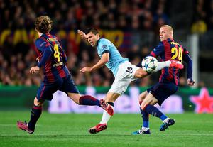 BARCELONA, SPAIN - MARCH 18: Sergio Aguero of Manchester City is challenged by Jeremy Mathieu (R) and Ivan Rakitic of Barcelona during the UEFA Champions League Round of 16 second leg match between Barcelona and Manchester City at Camp Nou on March 18, 2015 in Barcelona, Spain.  (Photo by Michael Regan/Getty Images)