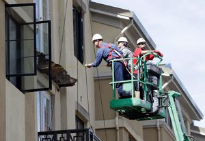 A worker measures near the remaining wood from an apartment building balcony that collapsed in Berkeley (AP Photo/Jeff Chiu)
