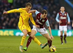 Burnley's Ashley Barnes  holds off Liverpool's Lucas Leiva during the Barclays Premier League match at Turf Moor, Burnley. Dave Thompson/PA Wire.