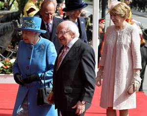 The President of Ireland Michael D. Higgins (centre) walks with Queen Elizabeth II (left) after arriving with his wife Sabina (right) at Windsor Castle in Berkshire during the president's state visit