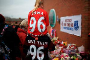 LIVERPOOL, ENGLAND - APRIL 15:  People leave tributes outside Anfield stadium before a memorial service to mark the 27th anniversary of the Hillsborough disaster, on April 15, 2016 in Liverpool, England. Thousands of fans, friends and relatives will take part in the final Anfield memorial service for the 96 victims of the Hillsborough disaster. Earlier this year relatives of the victims agreed that this year's service would be the last. Bells across the City of Liverpool will ring out during a one minute silence in memory of the 96 Liverpool supporters who lost their lives during a crush at an FA Cup semi-final match against Nottingham Forest at the Hillsborough football ground in Sheffield, South Yorkshire in 1989.  (Photo by Christopher Furlong/Getty Images)