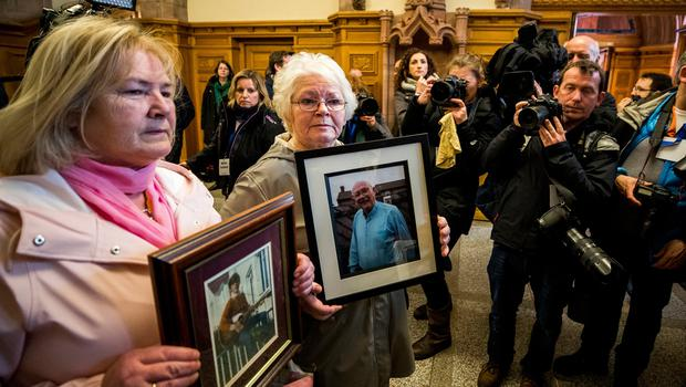 L-R Linda Nash, holds an image of their brother William Nash who was killed on Bloody Sunday, and Kate Nash holds an image of their father Alex Nash who was wounded on the day inside the Guildhall in Londonderry after the Public Prosecution Service announced that one solider will face prosecution for the murders of James Wray and William McKinney and the attempted murders of Joseph Friel, Michael Quinn, Joe Mahon and Patrick O'Donnell on Bloody Sunday in the city in January 1972. PRESS ASSOCIATION Photo. Picture date: Thursday March 14, 2019. See PA story ULSTER Sunday. Photo credit should read: Liam McBurney/PA Wire