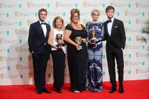 LONDON, ENGLAND - FEBRUARY 16:  Presenters Douglas Booth (R), Sam Claflin (L) pose with Kathrine Gordon, Lori McCoy-Bell and Evelyne Noraz, winners of the Make-Up and Hair award, in the winners room at the EE British Academy Film Awards 2014 at The Royal Opera House on February 16, 2014 in London, England.  (Photo by Anthony Harvey/Getty Images)