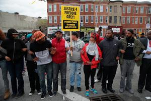 BALTIMORE, MD - APRIL 27:  Baltimore residents lock arms and form a line opposing police during violent protests at the corner of Pennsylvania and North avenues following the funeral of Freddie Gray April 27, 2015 in Baltimore, Maryland. Gray, 25, who was arrested for possessing a switch blade knife April 12 outside the Gilmor Homes housing project on Baltimore's west side. According to his attorney, Gray died a week later in the hospital from a severe spinal cord injury he received while in police custody.  (Photo by Chip Somodevilla/Getty Images)