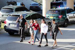 Teens, who walked out from the direction of the high school, are escorted by police following a shooting at Marjory Stoneman Douglas High School, Wednesday, Feb. 14, 2018, in Parkland, Fla. (Amy Beth Bennett/South Florida Sun-Sentinel via AP)